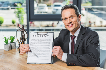 portrait of smiling lawyer pointing at contract in hand while sitting at workplace in office