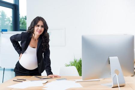 schwangere Geschäftsfrau mit Rückenschmerzen am Arbeitsplatz beim Betrachten des Computers