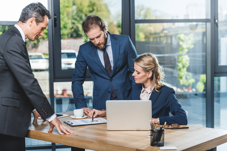 portrait of group of lawyers discussing work together at workplace with laptop in office