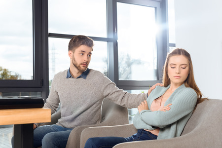 young couple quarreling while sitting on psychotherapy in office
