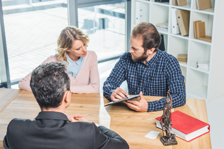 concentrated couple discussing contract together with lawyer in office
