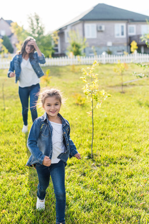 mother and daughter playing catch-up on beautiful garden