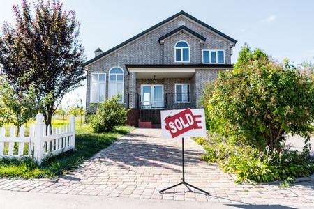 schönes Haus mit Schild verkauft auf dem Weg stehend
