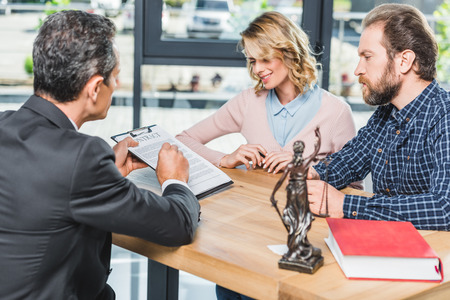 side view of couple discussing contract together with lawyer in office