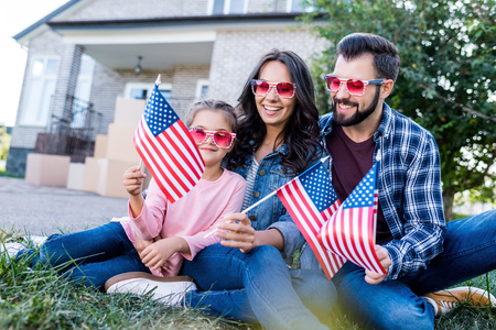 happy young family with american flags and sunglasses sitting in garden of new house