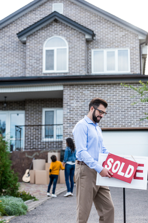 young realtor with sold signboard in front of people moving into new house Stock Photo