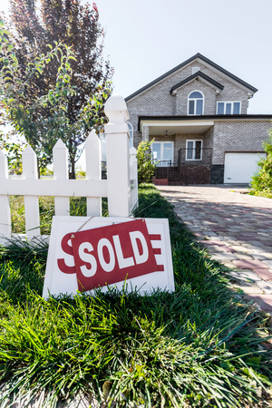beautiful house with sign sold leaning on fence