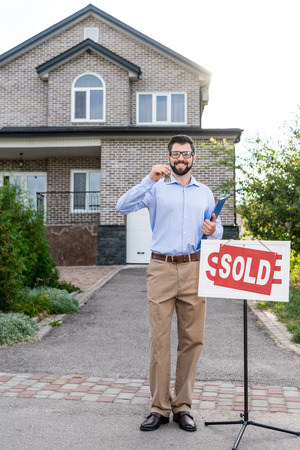 handsome smiling realtor with keys of sold house