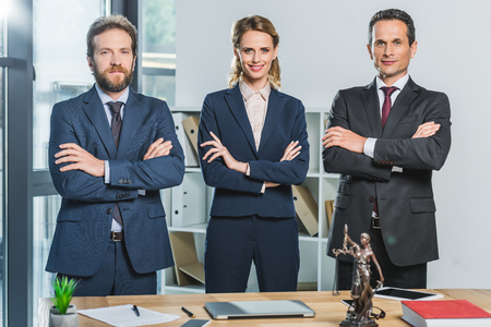 portrait of lawyers in suits with arms crossed looking at camera while standing at workplace