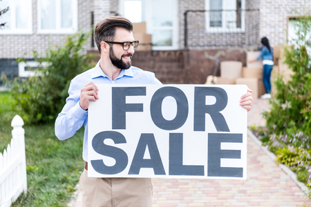 handsome young realtor with banner for sale in front of house Stock Photo