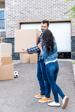 young stylish couple with boxes moving into new house