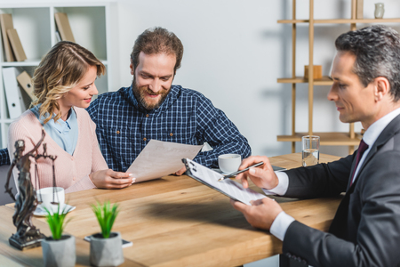 selective focus of smiling couple reading contract while having meeting with lawyer in office