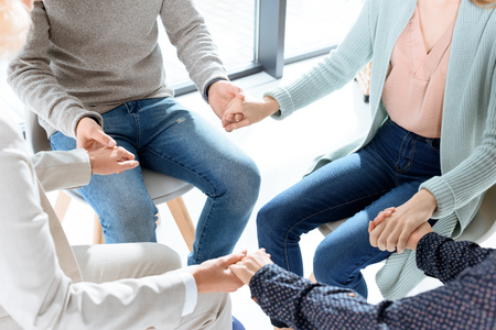 partial view of people holding hands during group therapy session