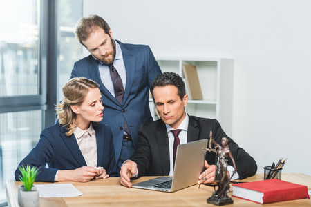 portrait of group of focused lawyers using laptop together in office