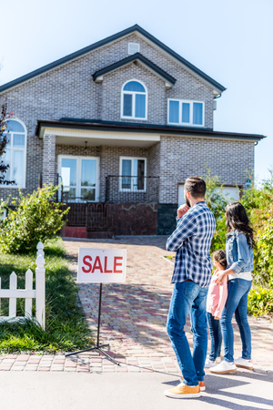 young beautiful family looking at house on sale and embracing Banque d'images - 102324116