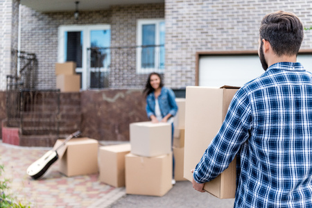 couple with cardboard boxes moving into new house Stock Photo