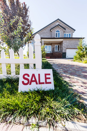beautiful house with sign sale leaning on fence Imagens