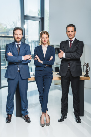 lawyers in suits with arms crossed looking at camera while standing at workplace in office Zdjęcie Seryjne