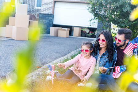 young family with american flags and sunglasses sitting in garden of new house