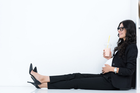 pregnant businesswoman drinking milkshake while sitting on floor