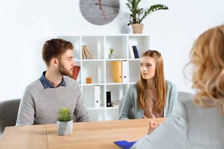 cropped shot of psychologist and serious young couple looking at each other during psychotherapy