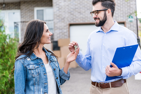 realtor giving keys from new house to young happy woman Stock Photo