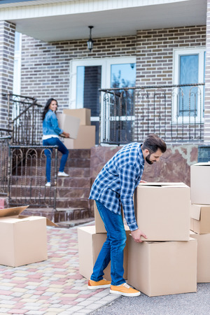 young couple with cardboard boxes moving into new house