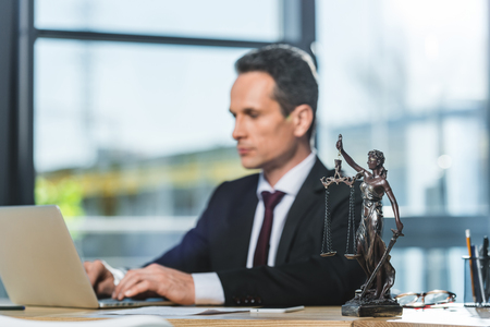 selective focus of focused lawyer working on laptop at workplace with femida in office