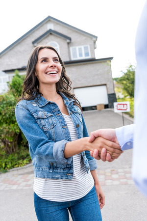 young happy woman shaking hands with realtor Stock Photo