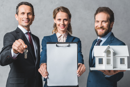 selective focus of smiling business people with house model, keys and folder looking at camera
