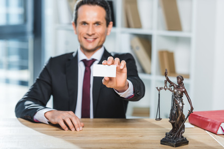 selective focus of smiling lawyer showing blank visit card in hand at workplace in office
