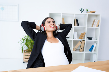 happy pregnant businesswoman relaxing and listening music in office with hands behind head Stock Photo