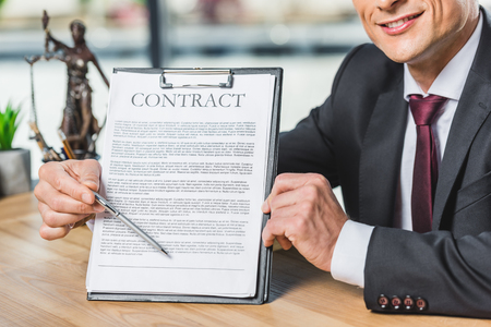 cropped shot of lawyer pointing at contract in hand while sitting at workplace in office