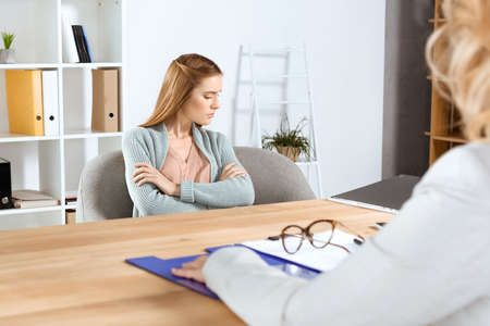 cropped shot of psychologist and young female patient sitting with crossed arms at therapy Stock Photo