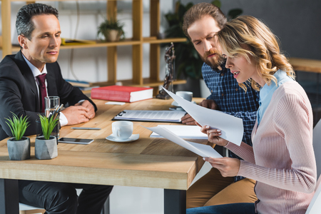 side view of concentrated couple reading contract during meeting with lawyer in office