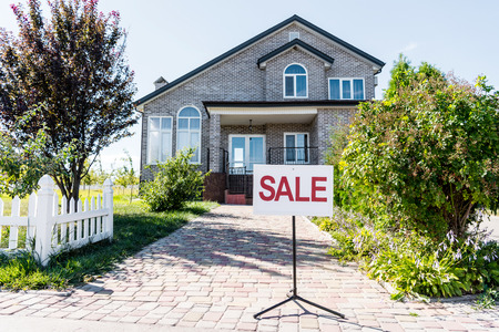 beautiful house with sign sale standing on pathway