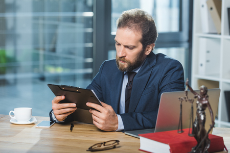 portrait of focused lawyer reading contract at workplace with laptop in office