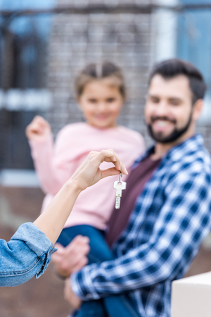woman showing key of new house to husband and daughter