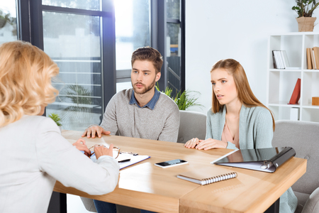 cropped shot of young couple looking at psychologist in office Stockfoto