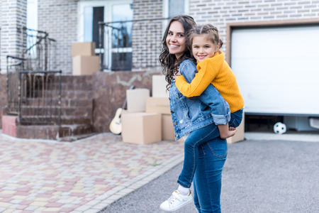 beautiful daughter piggyback riding young mother in front of new house Stok Fotoğraf - 102352484