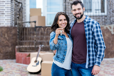 young couple with keys in front of new house