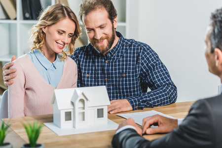 portrait of couple having meeting with realtor in real estate agency office Stock Photo