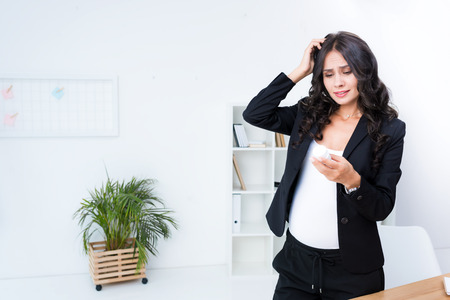 bewildered pregnant businesswoman looking at jar of pills
