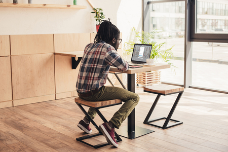 back view of african american man using laptop with linkedin website in coffee shop