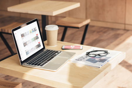 laptop, smartphone with youtube appliance and business newspaper on table in coffee shop Redactioneel