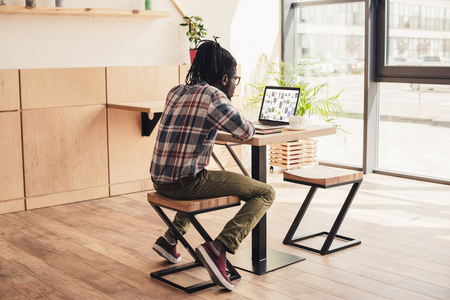 back view of african american man using laptop with pinterest website in coffee shop