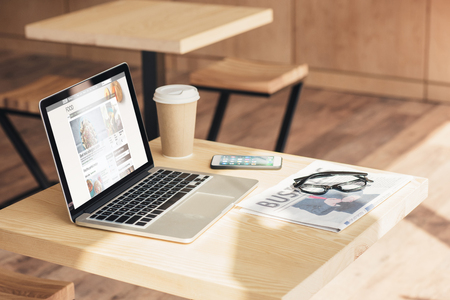laptop, smartphone and business newspaper on table in coffee shop Stok Fotoğraf - 105372300