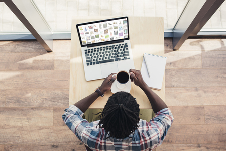 overhead view of african american man drinking coffee and using laptop with pinterest website