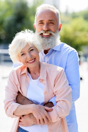 portrait of happy senior man hugging wife on street Stock Photo