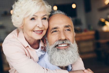 portrait of smiling senior woman hugging husband in cafe